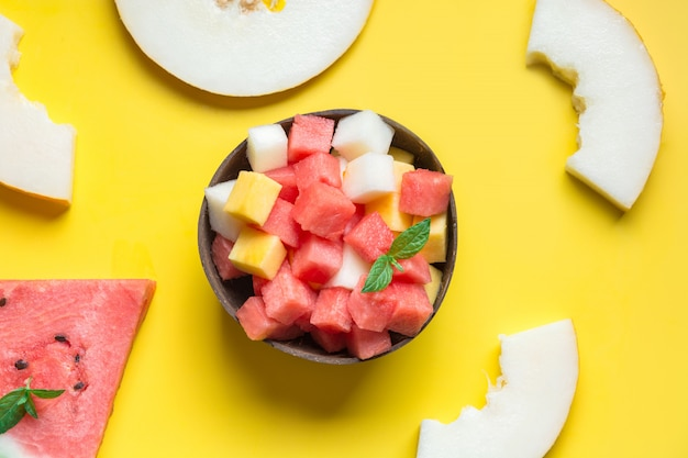Fruit salad of watermelon, melon and peach in coconut bowl in hands of child on yellow background.