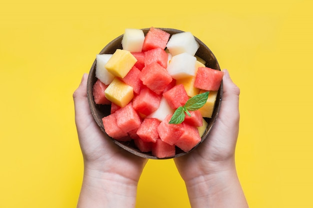 Fruit salad of watermelon, melon and peach in coconut bowl in hands of child