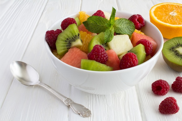Fruit salad in the white bowl closeup