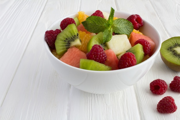 Fruit  salad in the white bowl on the white wooden background. closeup.