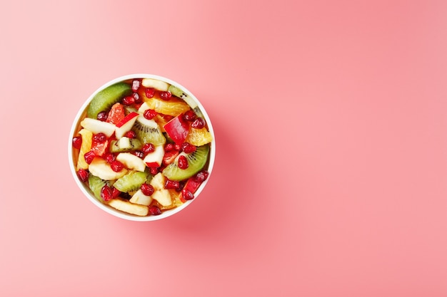 Fruit salad in a white cup on a pink background, free space for text. slices of fresh, juicy and healthy fruits for a healthy diet.