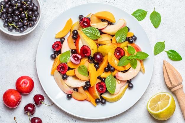 흰 접시, 흰색 배경, 평면도에 딸기와 과일 샐러드. 건강한 채식 음식 개념.