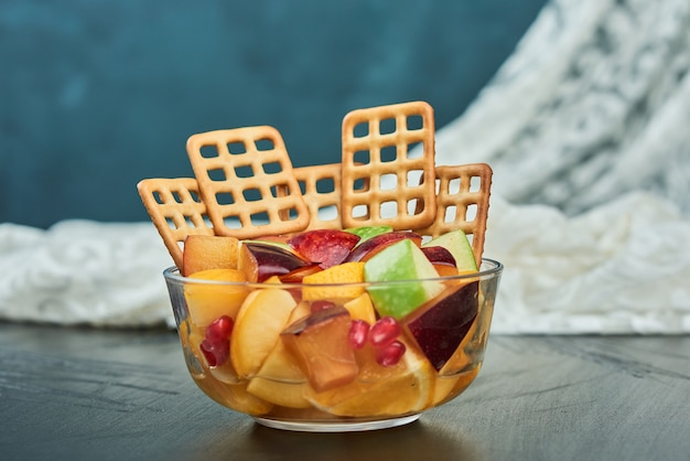 Macedonia di frutta con cracker in una tazza.