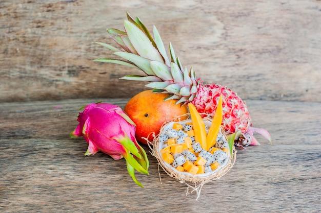 半分のココナッツのドラゴンフルーツとパパイヤのフルーツサラダ