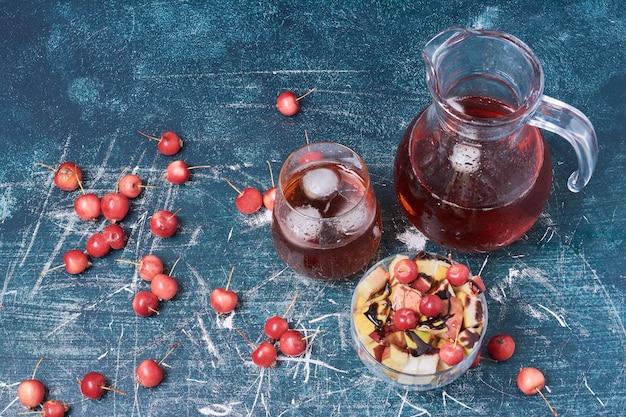 Macedonia di frutta con un bicchiere di succo rosso sull'azzurro.