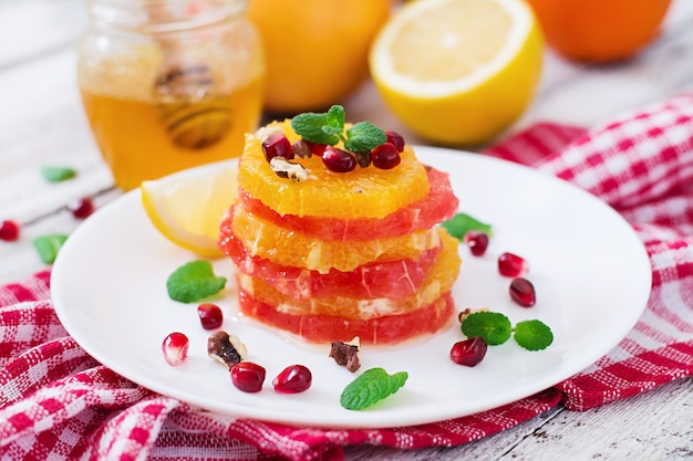 Fruit salad with grapefruit and orange, pomegranate seeds, honey and lemon, decorated with mint