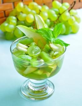 ミントの葉で飾られた、グラスにワインをトッピングしたブドウ、キウイ、洋ナシのフルーツサラダ。