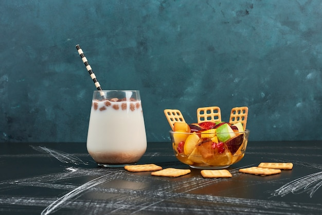 Fruit salad with milk and crackers.