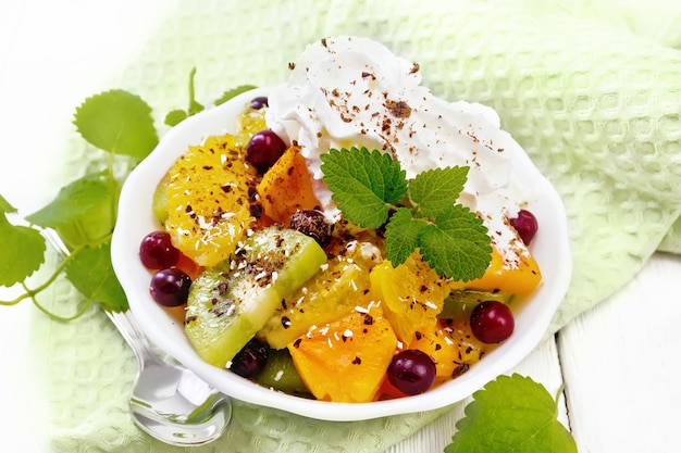 오렌지, 키위, 크랜베리, 구운 호박을 곁들인 과일 샐러드, 휘핑크림, 초콜릿과 코코넛을 뿌린 민트 그릇에 밝은 나무 판자를 배경으로 한 그릇에