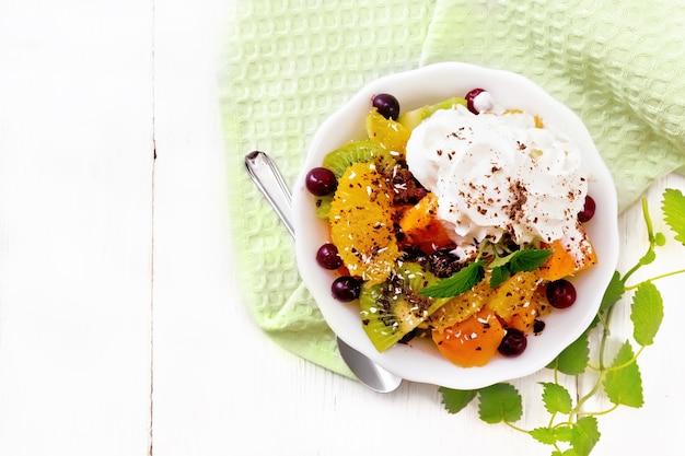 Фруктовый салат с апельсином, киви, клюквой и запеченной тыквой, взбитыми сливками, посыпанными шоколадом и кокосом с мятой в миске на полотенце на фоне деревянной доски сверху