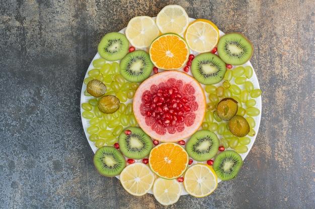 Фруктовый салат с гранатом, грейпфрутом и киви на белой тарелке. фото высокого качества