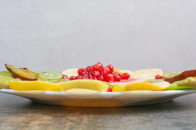 Fruit salad with pomegranate, grapefruit and kiwi on white plate. high quality photo
