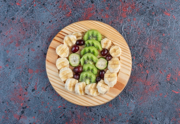 Fruit salad with sliced banana, kiwies and berries in a wooden plate.