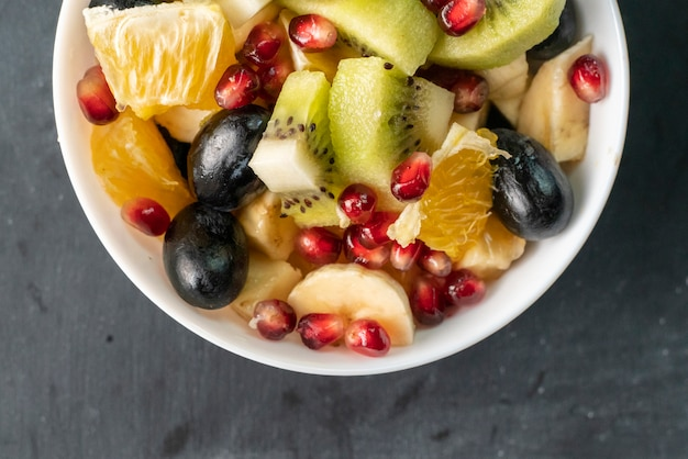 Fruit salad with tropical exotic ripe fruits chopped in cubes, orange, kiwi, banana, grapes, pomegranates