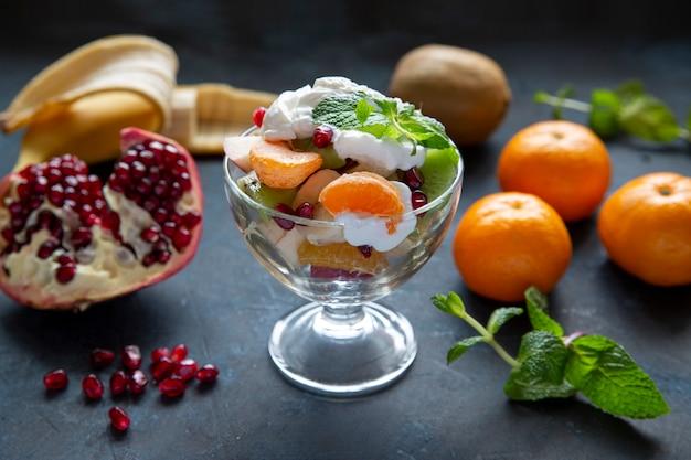 Фруктовый салат с йогуртом и яркими фруктами на темном фоне стола. гранат, банан, киви, мандарины, листья мяты. здоровое питание. вегетарианская еда