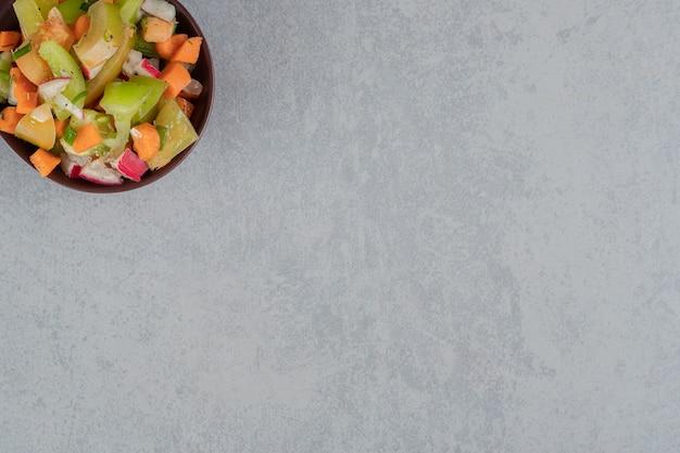 Macedonia di frutta in una tazza di legno su una superficie di cemento