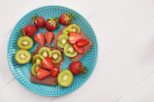 Fruit sandwich, strawberries and kiwi. peanut butter toast.
