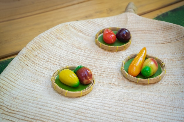 Fruit shaped mung beans - kanom look choup, thai sweet applied vintage - modern on the wicker plate