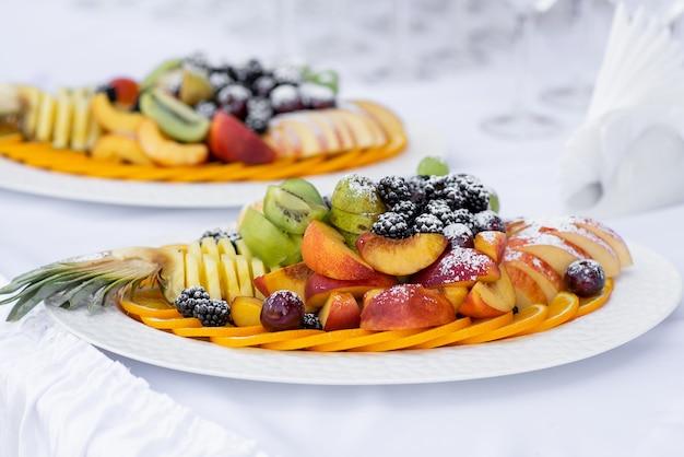 粉砂糖をまぶした白い皿にスライスしたフルーツ