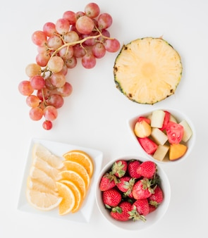 Fruit slices of orange; lemon; watermelon; pineapple; strawberries and bunch of grapes on white backdrop
