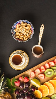 Fruit slices with tea and fresh walnut bowl on table