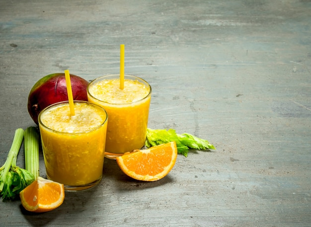 Fruit smoothie in glasses on rustic table.