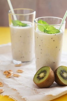 Fruit smoothie in glasses with milk and kiwi