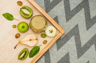 Fruit smoothie on wooden tray over the tablecloth