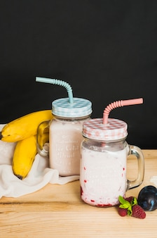 Fruit smoothies in closed jar with blue and pink straws against black background