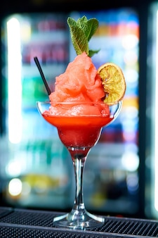Fruit sorbet in a glass on a blurred background.