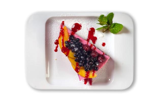 白い背景に分離されたソースとブルーベリーのフルーツスフレ。自家製の夏のデザート。