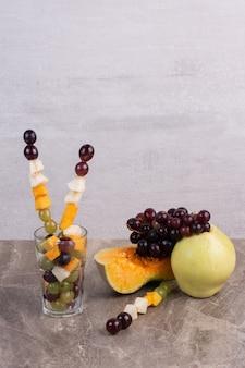 Фруктовые палочки и свежие фрукты на мраморной поверхности.