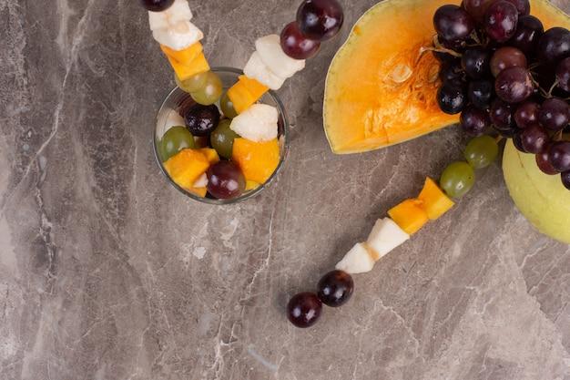 Bastoncini di frutta e frutta fresca sulla superficie in marmo.