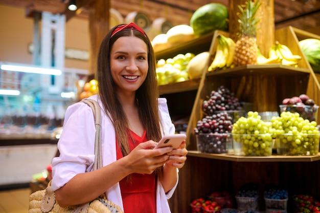 과일 가게. 과일 가게에서 귀여운 젊은 여성