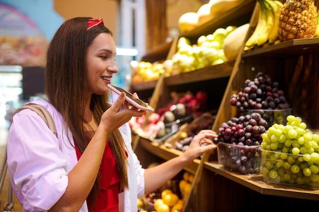 과일 가게. 가게에서 과일을 고르는 젊은 여성