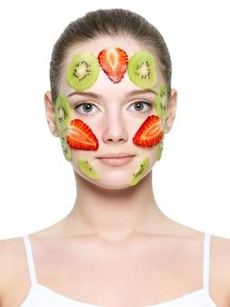 白で隔離される美しい女性の若い顔にイチゴとキウイのフルーツイチゴマスク