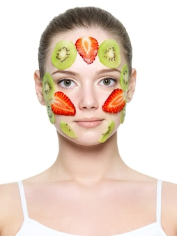 Fruit strawberry mask of strawberry and kiwi on a young face of beautiful woman isolated on white
