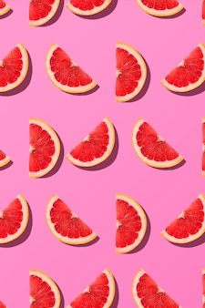 Fruit summer pattern. flat lay composition grapefruit slice close up on pink background