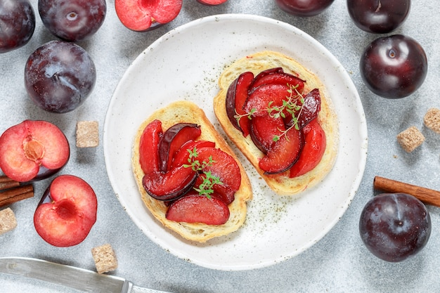 Fruit sweet bruschetta with caramel plums, cinnamon and thyme