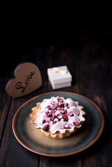 Fruit tart on plate with heart and gift