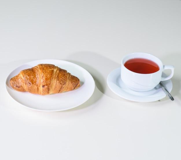아늑한 커피 숍의 테이블에 과일 차와 맛있는 신선한 크로와상