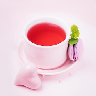 Фруктовый чай, макароны с ежевикой и розовое керамическое сердце на бледно-розовом