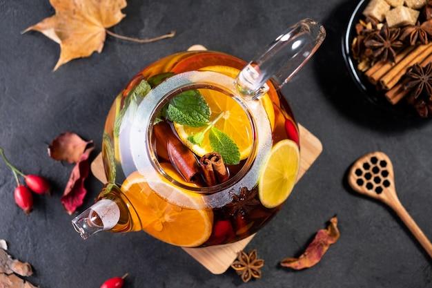 フルーツティー。季節の冬秋ホットドリンク。暗いテーブルの上のガラスのティーポットにレモン、オレンジ、ミントと柑橘類とベリーのお茶