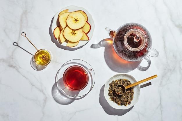ガラスのティーポットとハードシャドウと白い背景の上のカップにリンゴとタイムと蜂蜜とフルーツティー