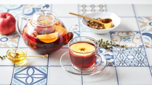 ガラスのティーポットにリンゴとタイムを入れたフルーツ ティーと、色付きのタイルで作られたテーブルの上のカップ