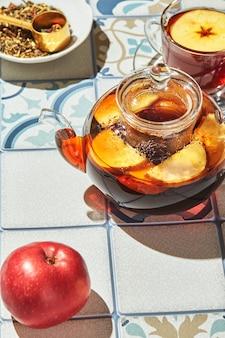 ガラスのティーポットと色のタイルで作られたテーブルの上のカップにリンゴとタイムのフルーツティー