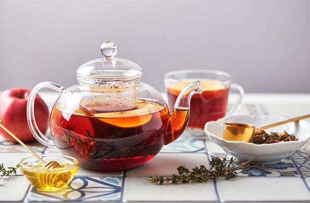 Фруктовый чай с яблоками и тимьяном в стеклянном чайнике и чашке на столе из цветной плитки