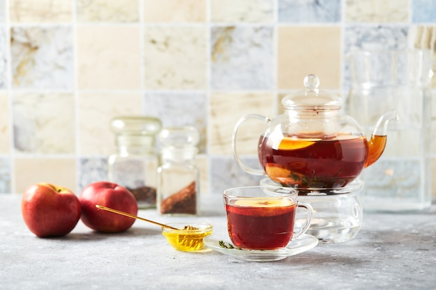 リンゴとタイムをガラスのティーポットに入れたフルーツ ティーと、キッチン テーブルの上のカップ