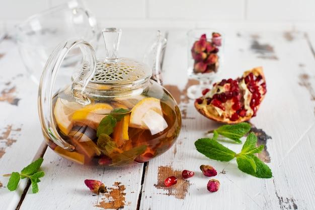 Фруктовый чай с ягодами, лимоном, лаймом и листьями мяты в стеклянном чайнике на белом светлом деревянном фоне. выборочный фокус.
