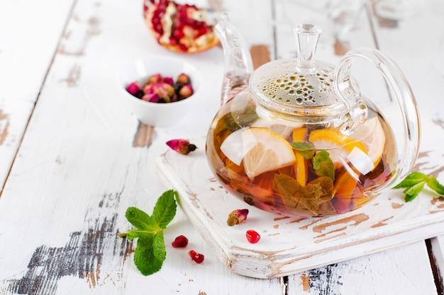 Фруктовый чай с ягодами, лимоном, лаймом и листьями мяты в стеклянном чайнике на белом светлом деревянном фоне.